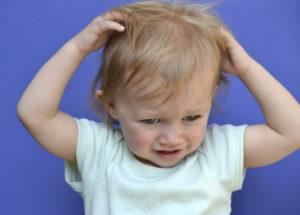 Ребенок чешет голову